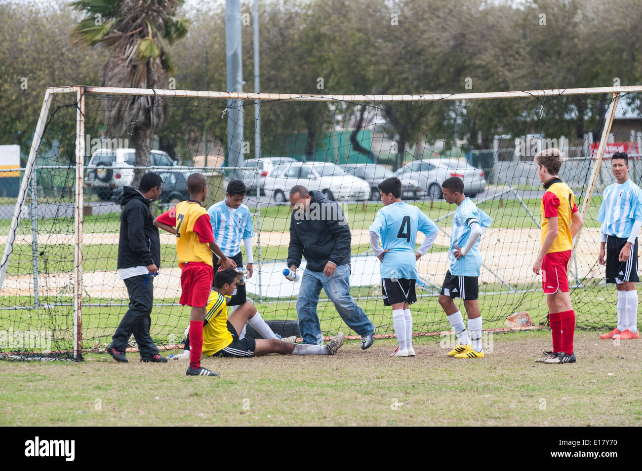 Injured junior football goalkeeper receiving treatment, players watching, Cape Town, South Africa - Stock Image