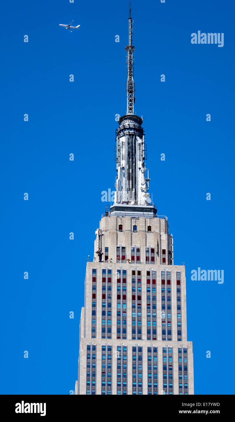 Tower of the Empire State Building in New York City with a jetliner passing overhead - Stock Image