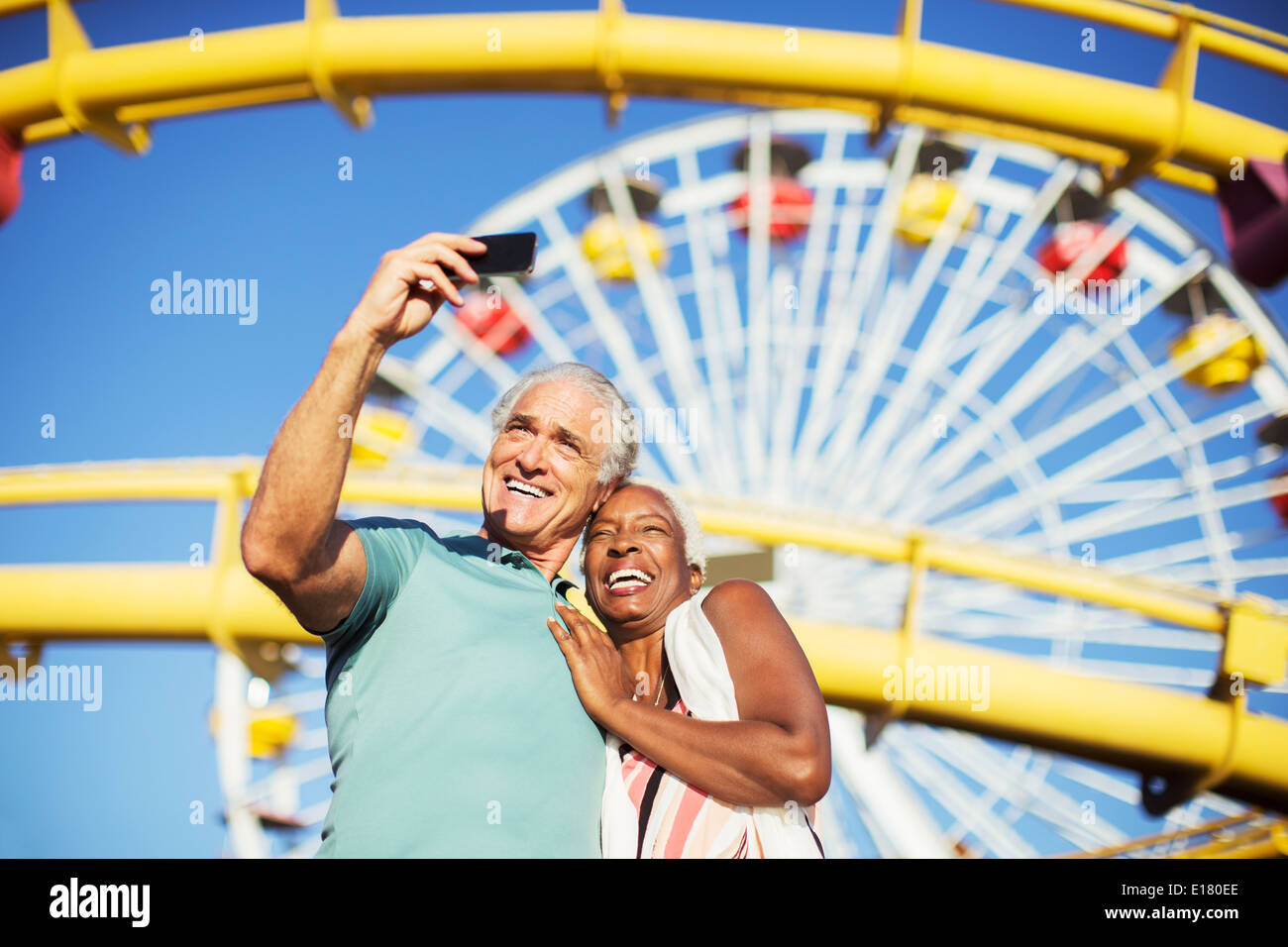 Senior couple taking selfie at amusement park - Stock Image
