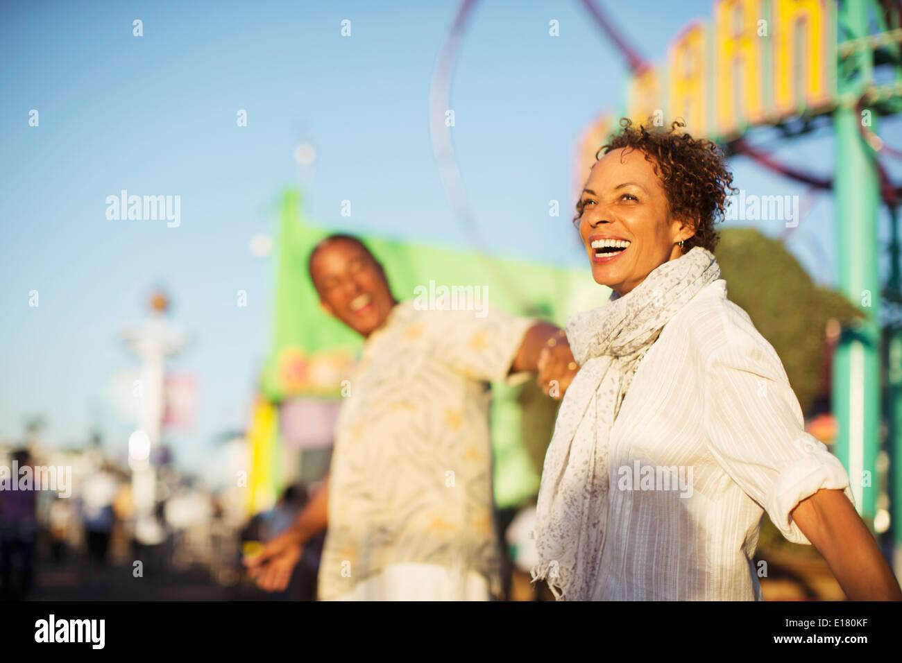 Enthusiastic couple at amusement park - Stock Image