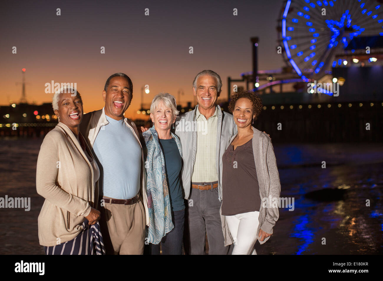 Portrait of senior friends on beach at night - Stock Image