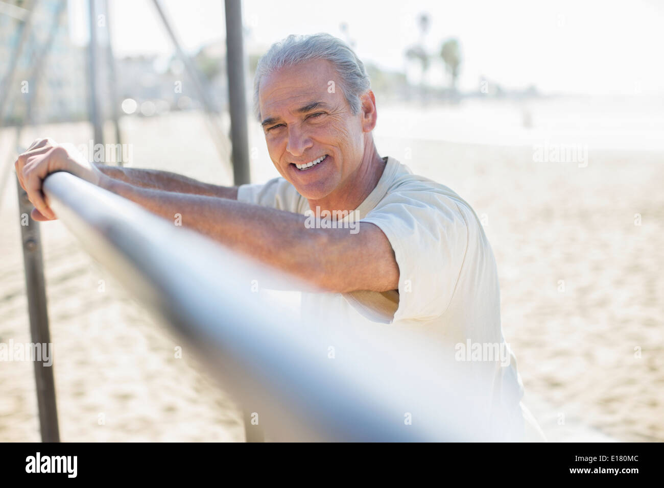 Portrait of senior man leaning on bar at beach - Stock Image