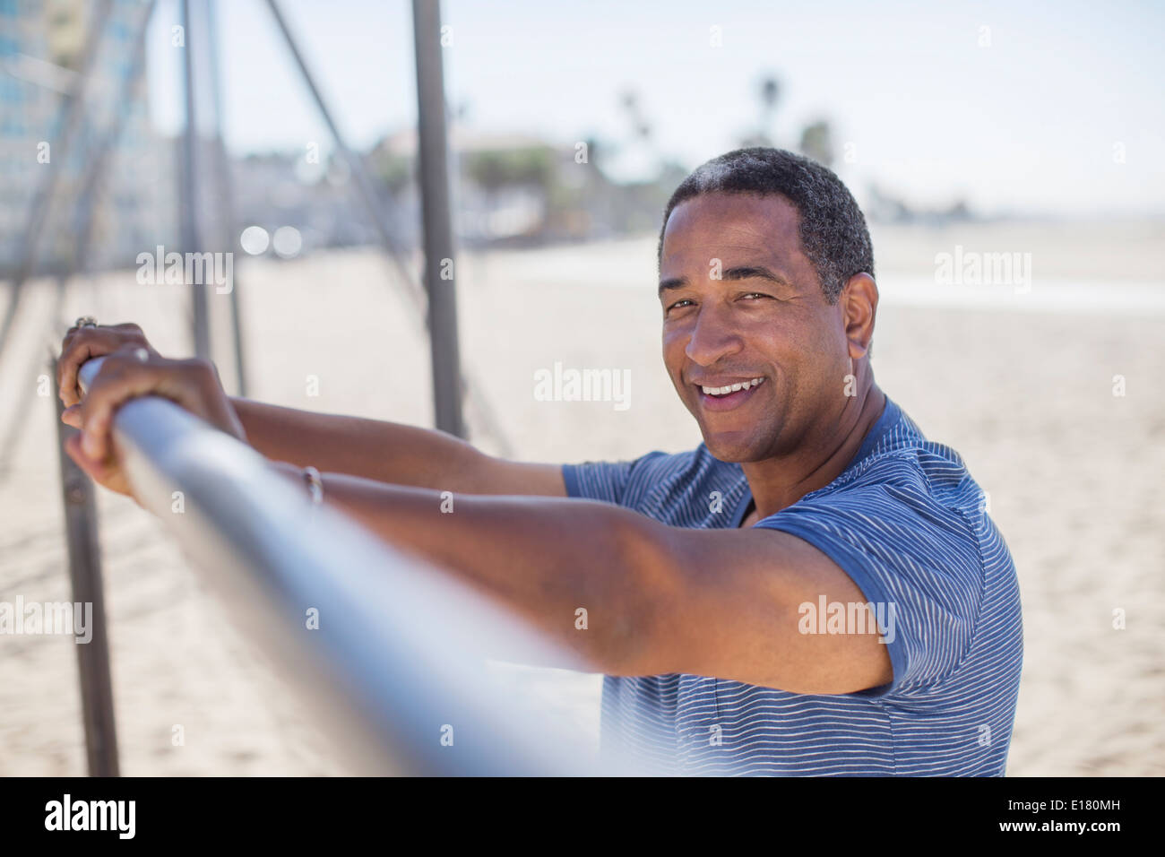 Portrait of senior man leaning on bar at beach playground - Stock Image