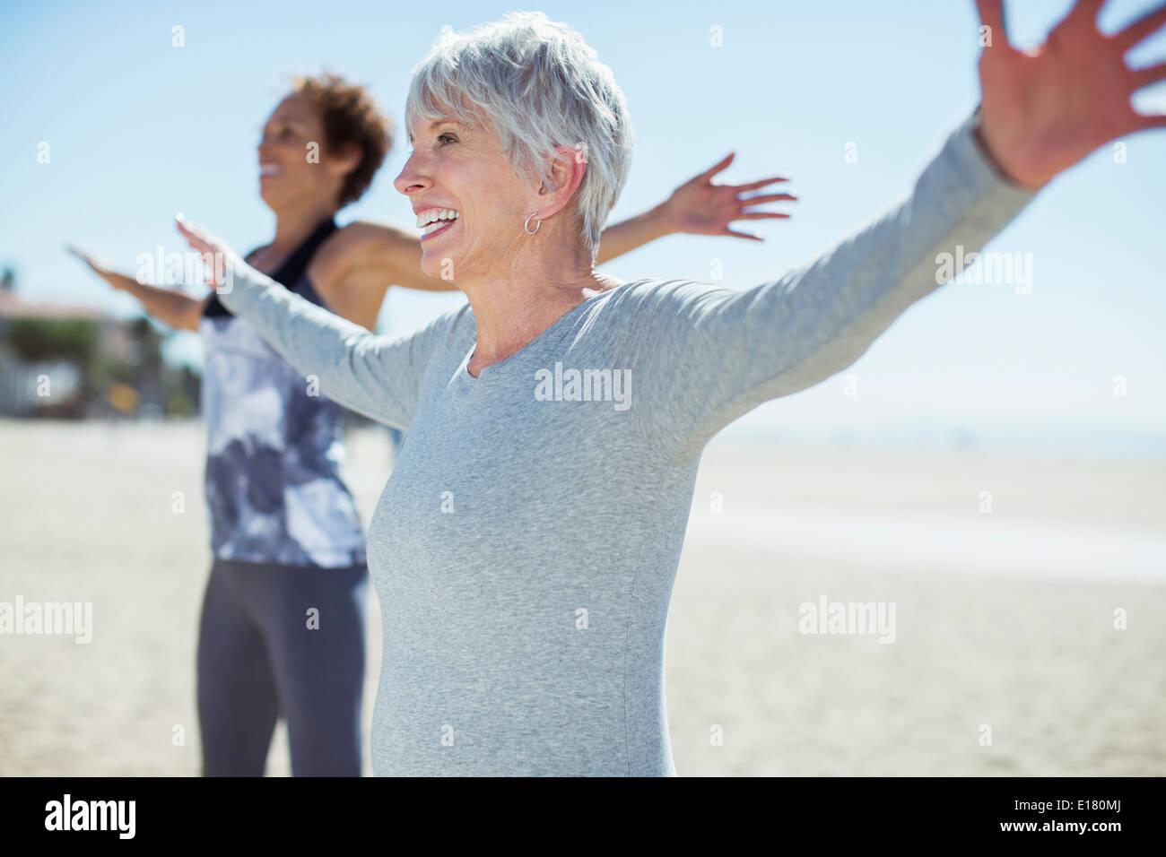 Senior women stretching arms on beach - Stock Image