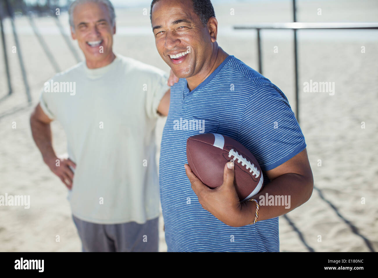 Portrait of senior men with football on beach - Stock Image