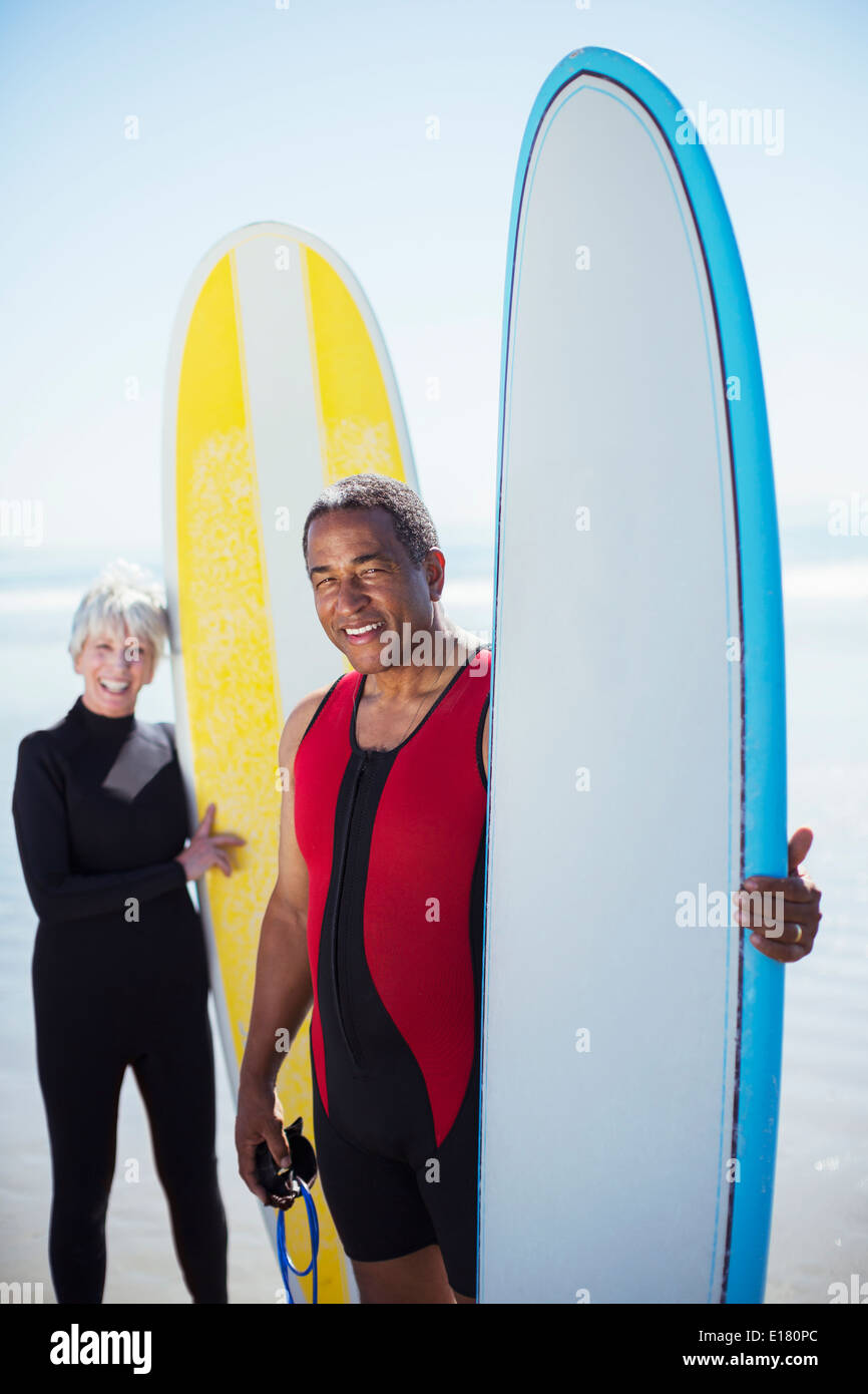 Portrait of senior couple with surfboards - Stock Image