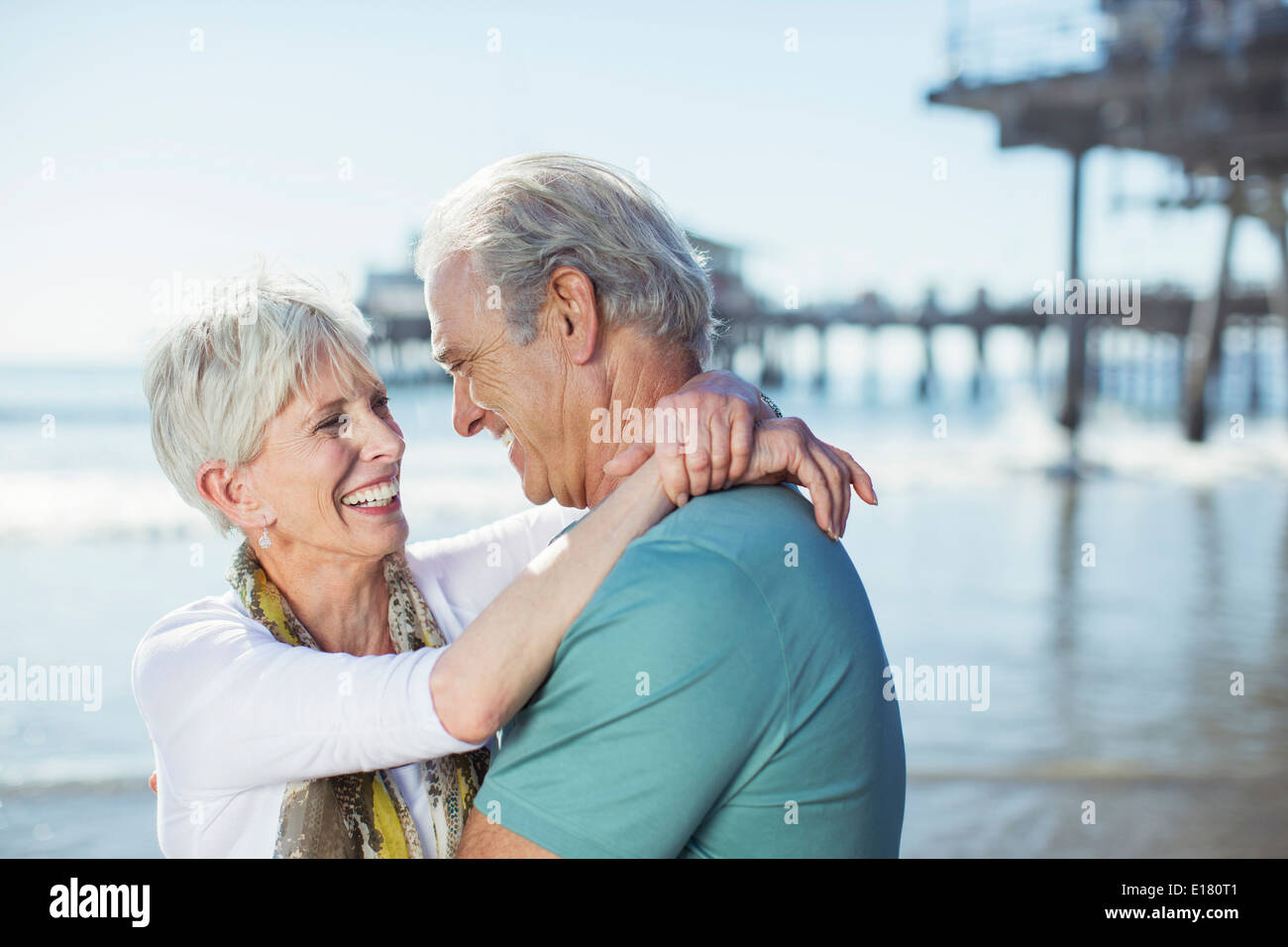 Senior couple hugging on beach - Stock Image