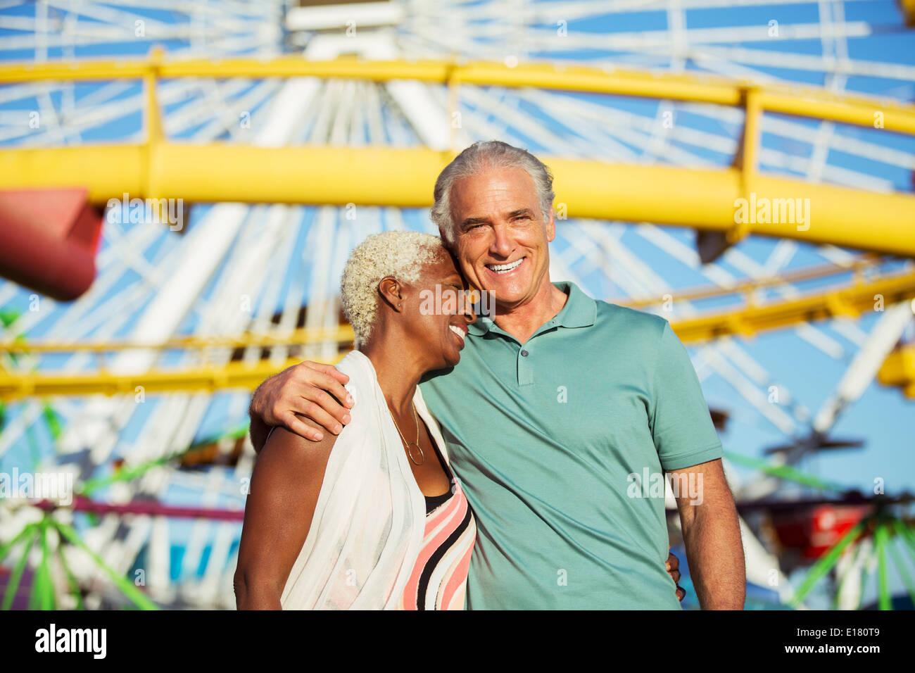 Portrait of hugging senior couple at amusement park - Stock Image