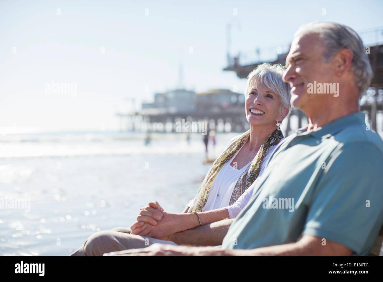 Senior couple relaxing on sunny beach - Stock Image