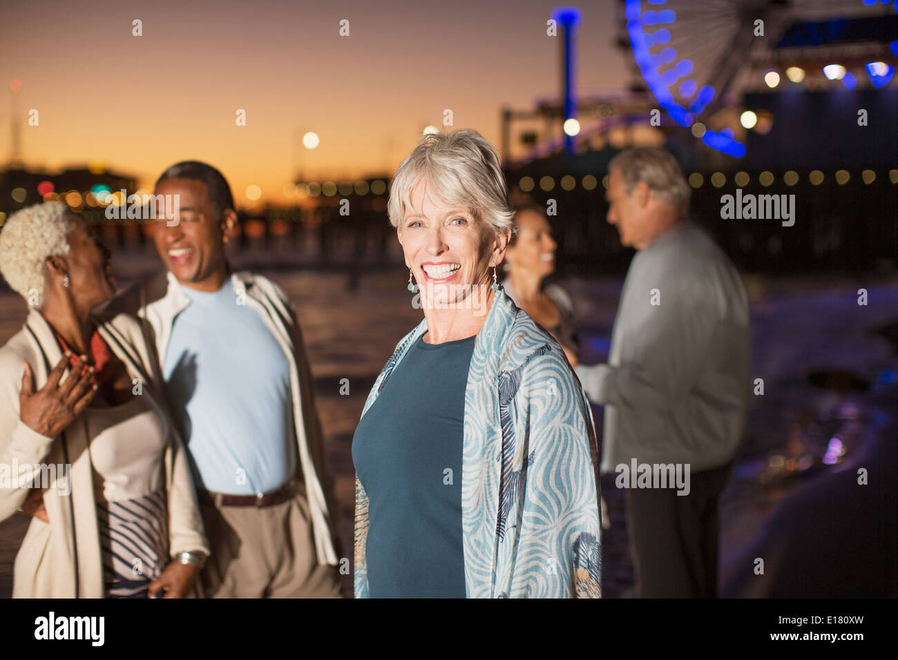 Portrait of enthusiastic senior woman with friends on beach at night Stock Photo
