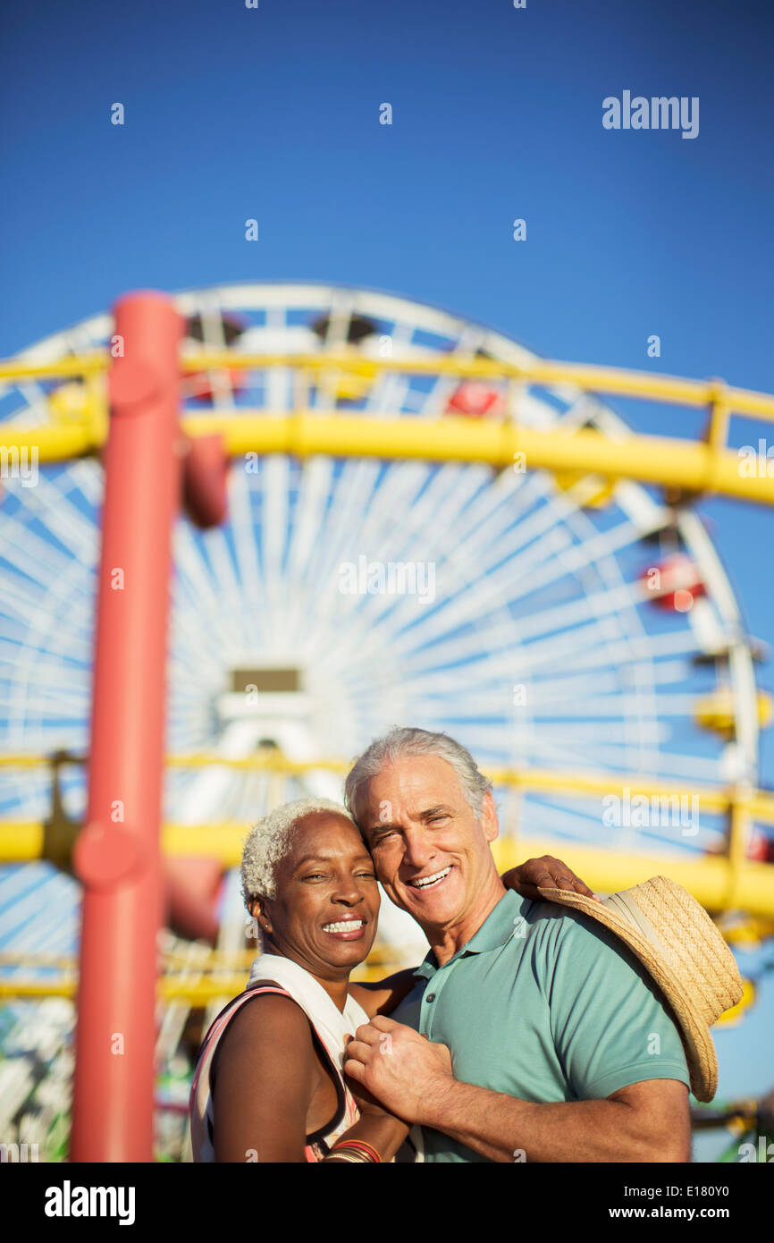 Portrait of happy senior couple hugging at amusement park - Stock Image