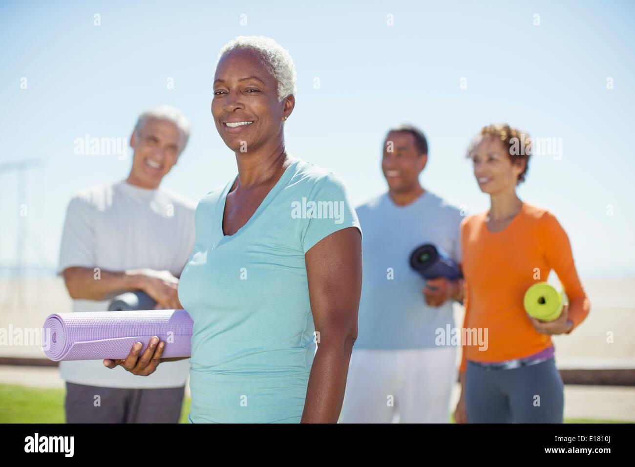 Portrait of confident senior woman with yoga mat in park - Stock Image