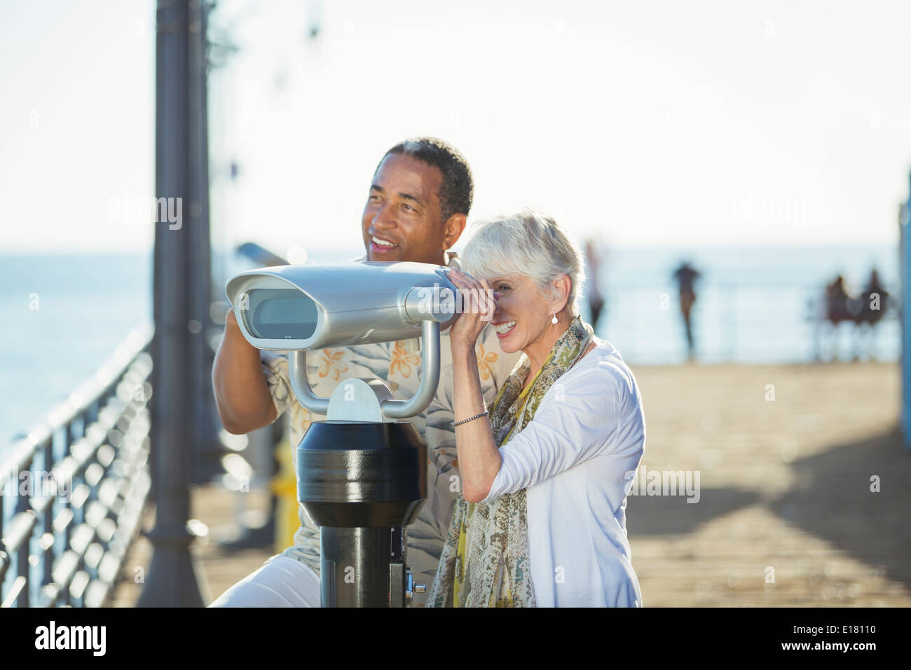 Senior couple using coin-operated binoculars on pier - Stock Image