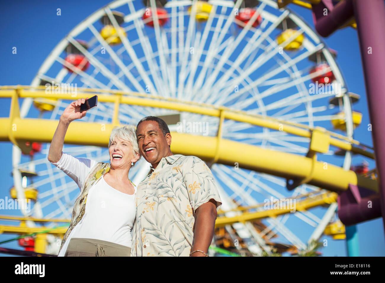 Enthusiastic senior couple taking selfie at amusement park - Stock Image
