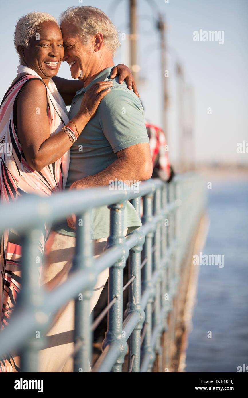 Senior couple hugging on pier - Stock Image