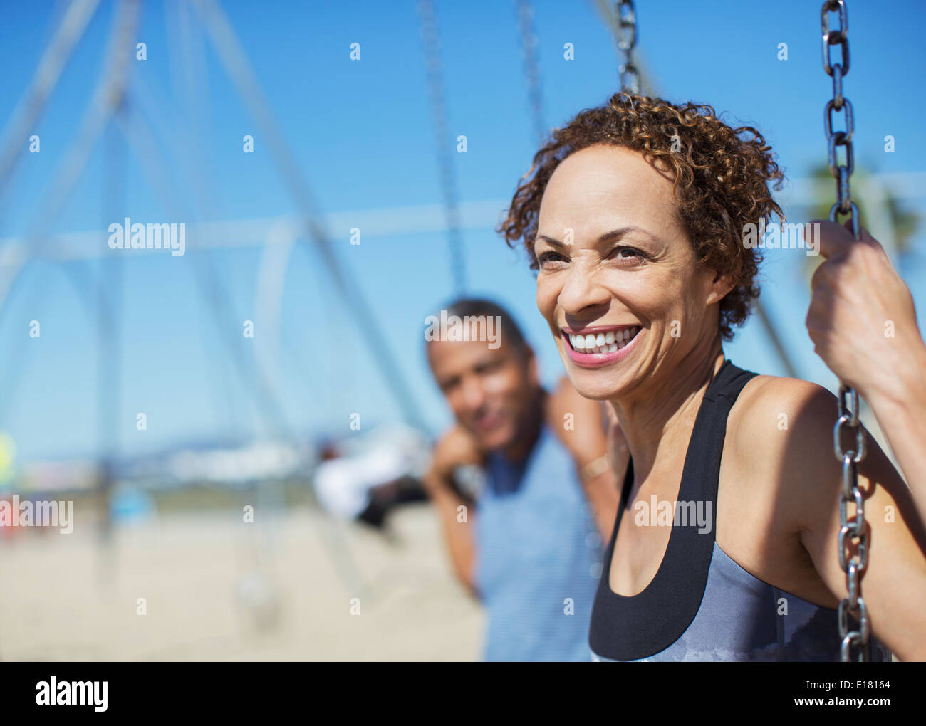 Happy couple on swings at playground - Stock Image