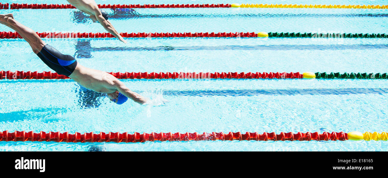 Swimmers diving into pool - Stock Image