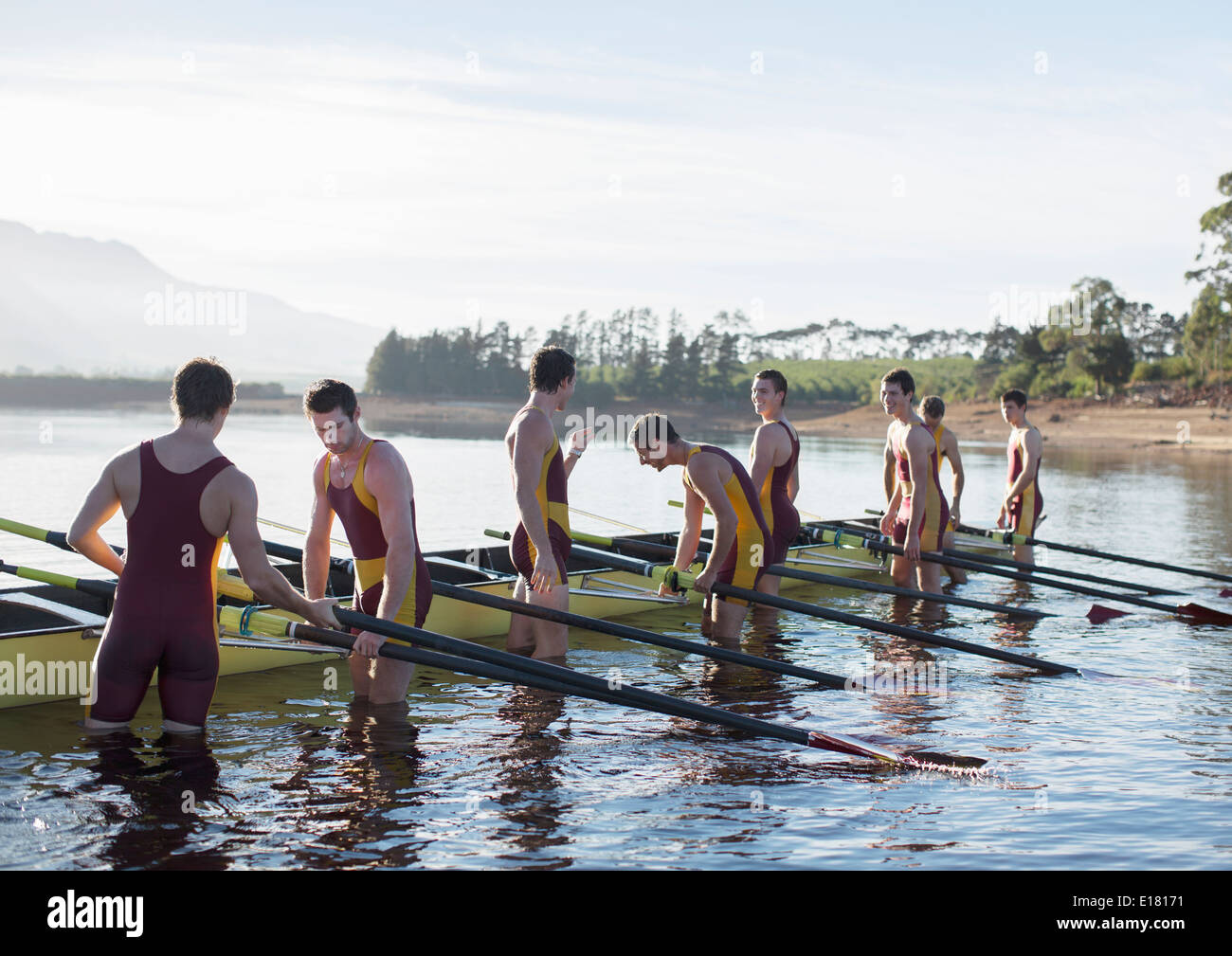 Rowing team placing boat on lake - Stock Image