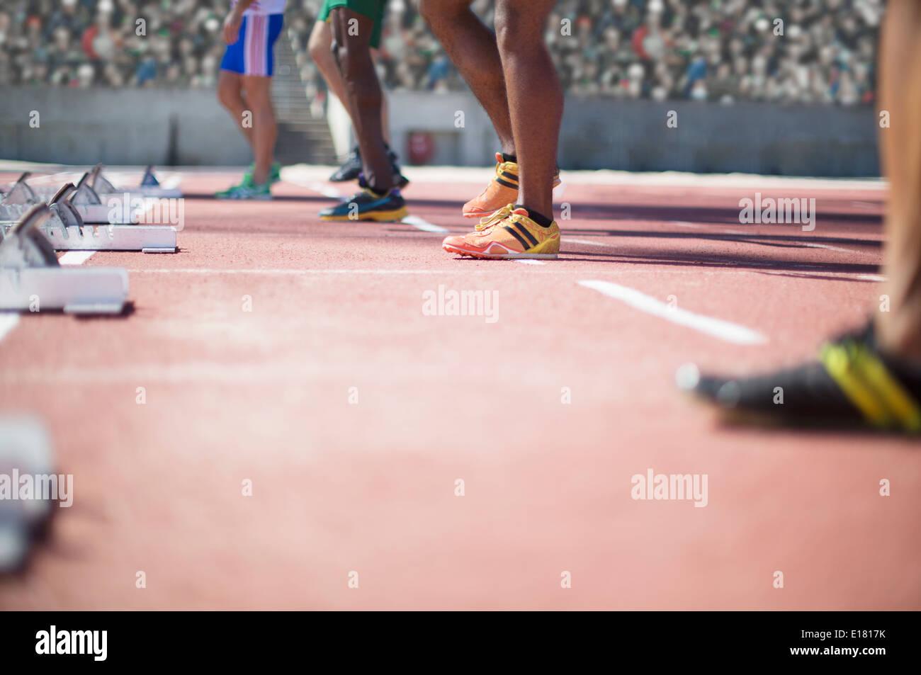 Runners standing at starting blocks on track - Stock Image