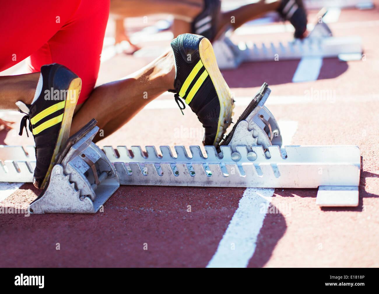 Runner's feet in starting blocks on track - Stock Image