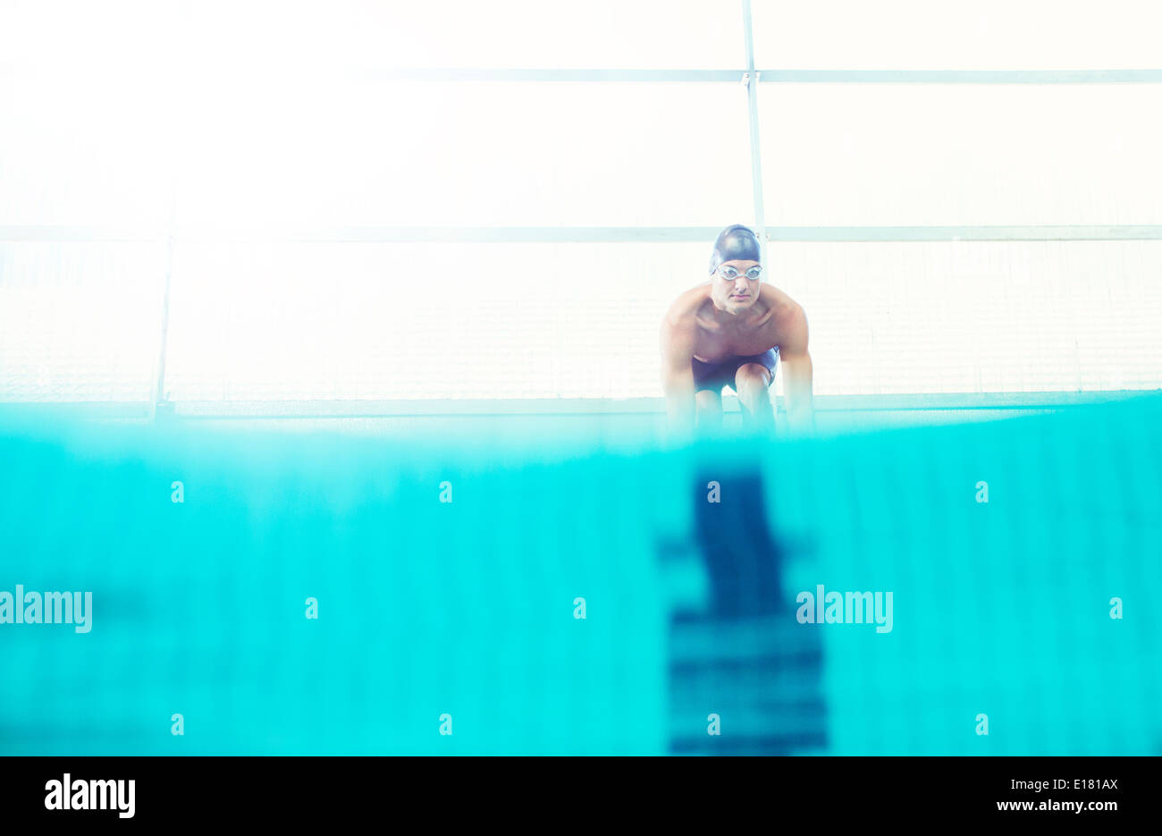 Swimmers poised on starting blocks - Stock Image
