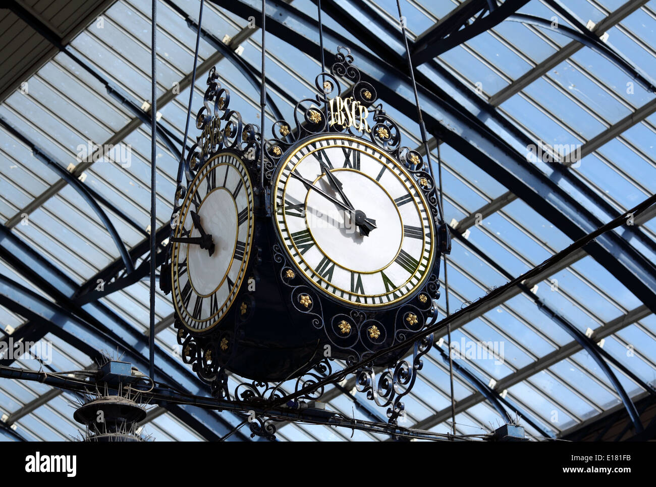 Ornate old clock hanging from the roof in Brighton station. - Stock Image
