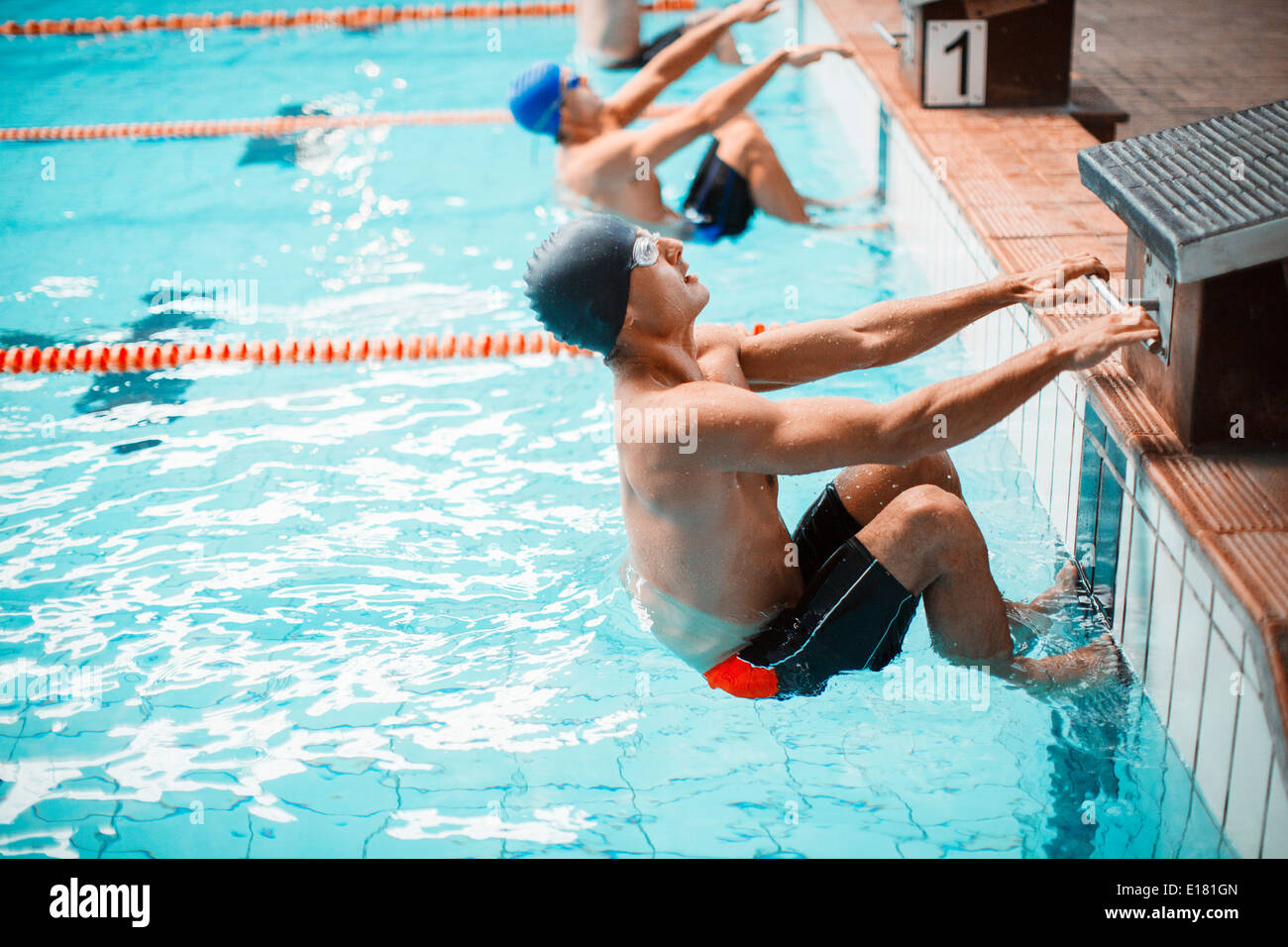 Swimmers poised at starting block in pool - Stock Image