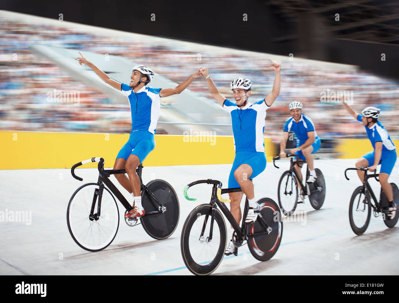Track cycling team celebrating in velodrome - Stock Image