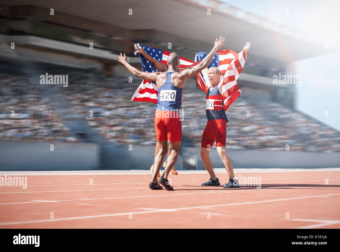 Runners celebrating and holding American flags on track - Stock Image