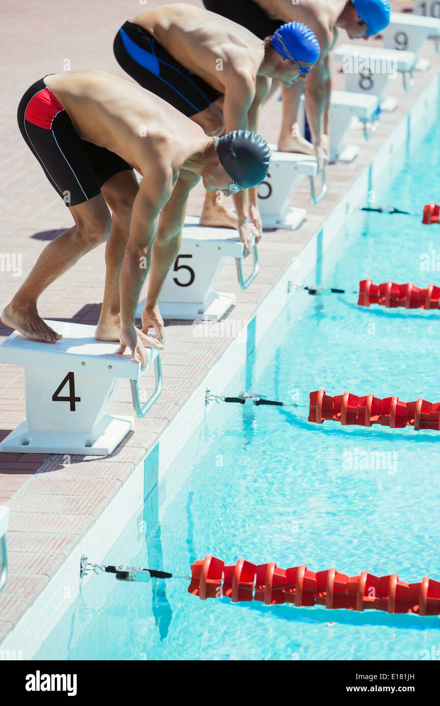Swimmers poised at starting blocks - Stock Image