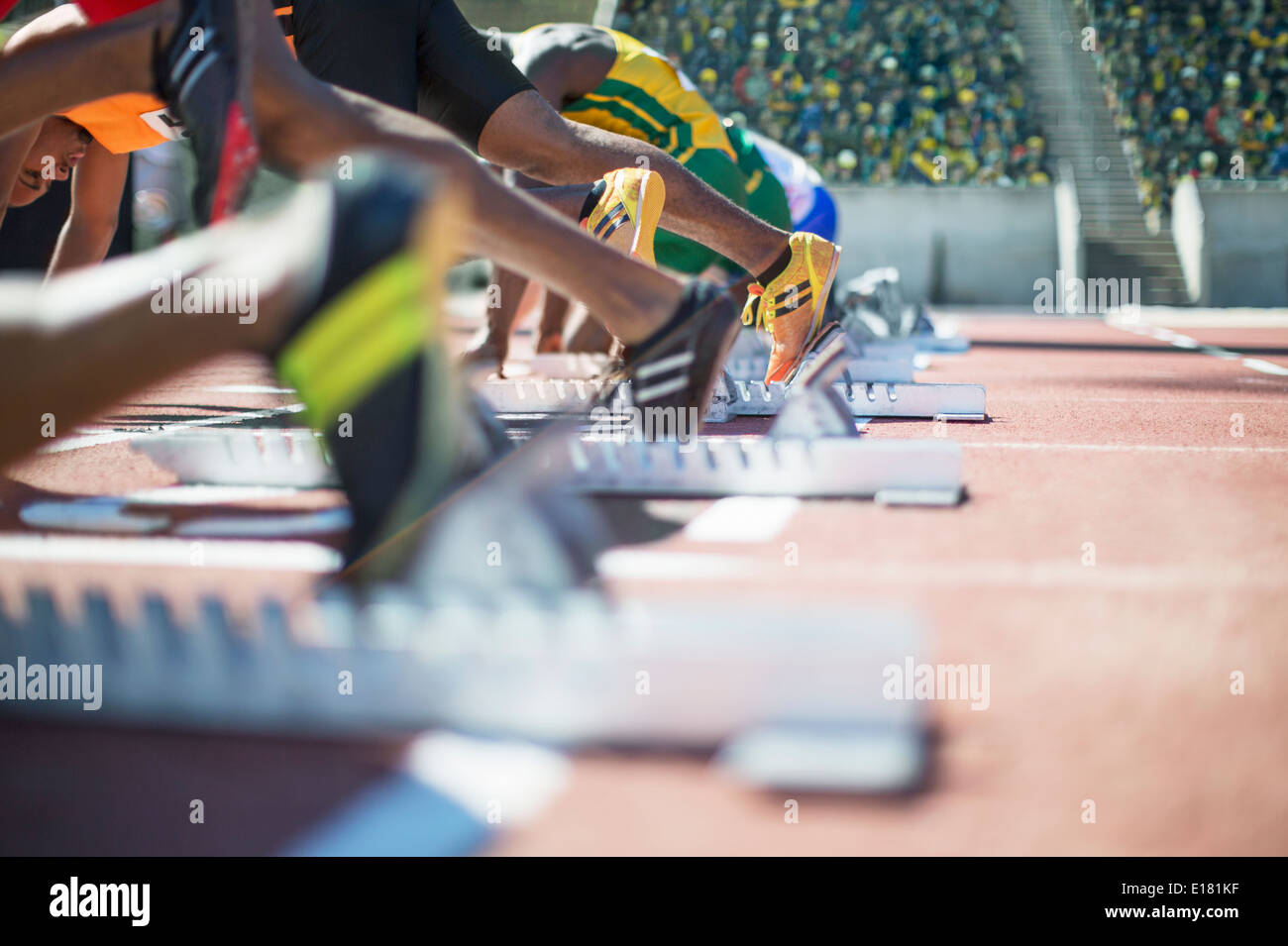 Runners poised at starting blocks on track - Stock Image
