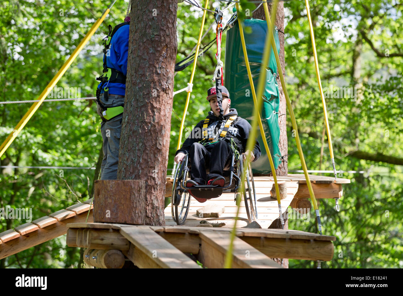 Schwarzenbruck, Germany. 14th May, 2014. Johannes Waltinger rolls over an obstacle in his wheelchair at the forest ropes course (Waldseilpark) in Schwarzenbruck, Germany, 14 May 2014. Two high ropes courses in Germany now offer their experience to persons with disabilities, too. This is made possible by specially trained helpers. Photo: Daniel Karmann/dpa/Alamy Live News - Stock Image