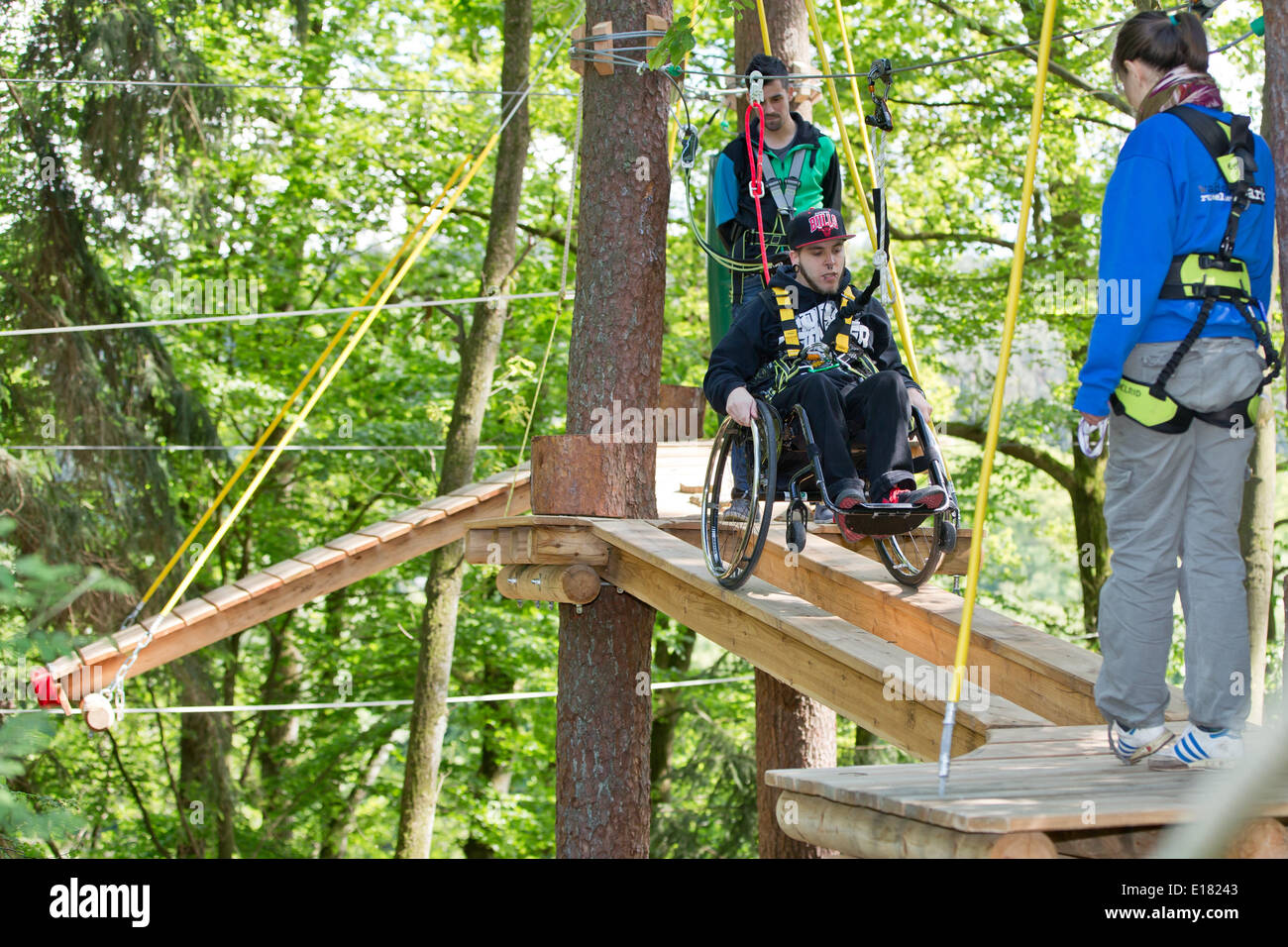 Schwarzenbruck, Germany. 14th May, 2014. Johannes Waltinger (C) rolls over an obstacle in his wheelchair at the forest ropes course (Waldseilpark) in Schwarzenbruck, Germany, 14 May 2014. Two high ropes courses in Germany now offer their experience to persons with disabilities, too. This is made possible by specially trained helpers. Photo: Daniel Karmann/dpa/Alamy Live News - Stock Image