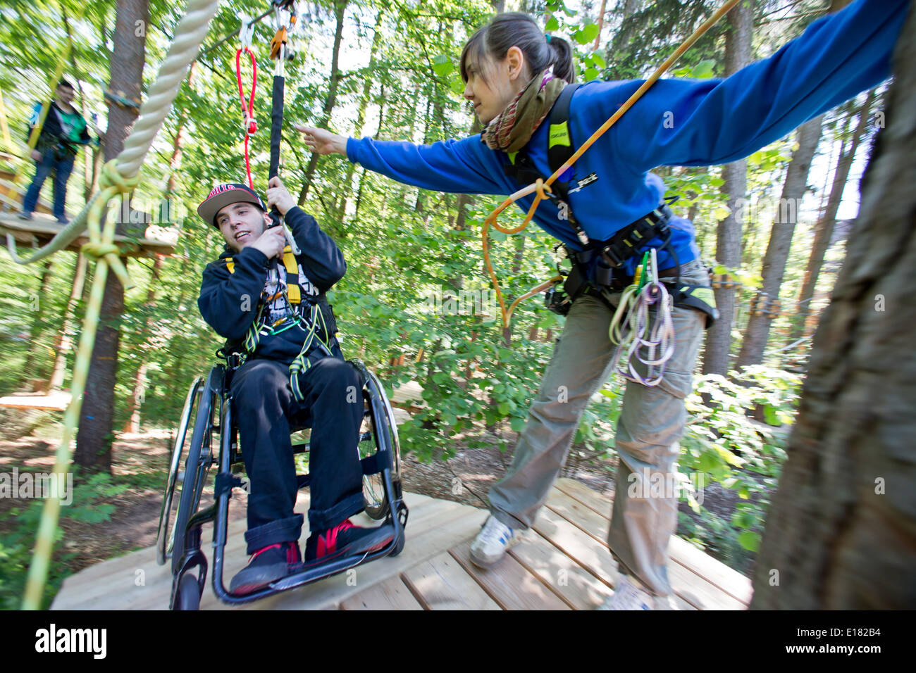 Schwarzenbruck, Germany. 14th May, 2014. Johannes Waltinger soars along a zip line in his wheelchair and is assisted by trainer Andrea Kammerer at the forest ropes course (Waldseilpark) in Schwarzenbruck, Germany, 14 May 2014. Two high ropes courses in Germany now offer their experience to persons with disabilities, too. This is made possible by specially trained helpers. Photo: Daniel Karmann/dpa/Alamy Live News - Stock Image