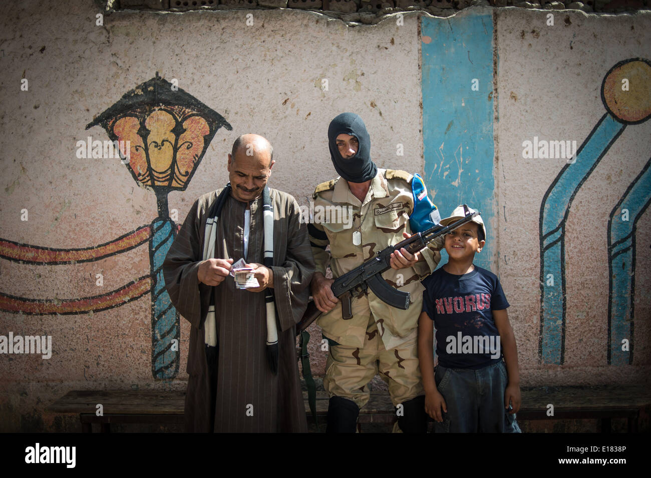 Cairo, Egypt. 26th May, 2014. An Egyptian army solider poses with a boy and a vendor inside a polling station in Cairo, Egypt, on May 26, 2014. Egypt held presidential election on Monday. Credit:  Pan Chaoyue/Xinhua/Alamy Live News - Stock Image