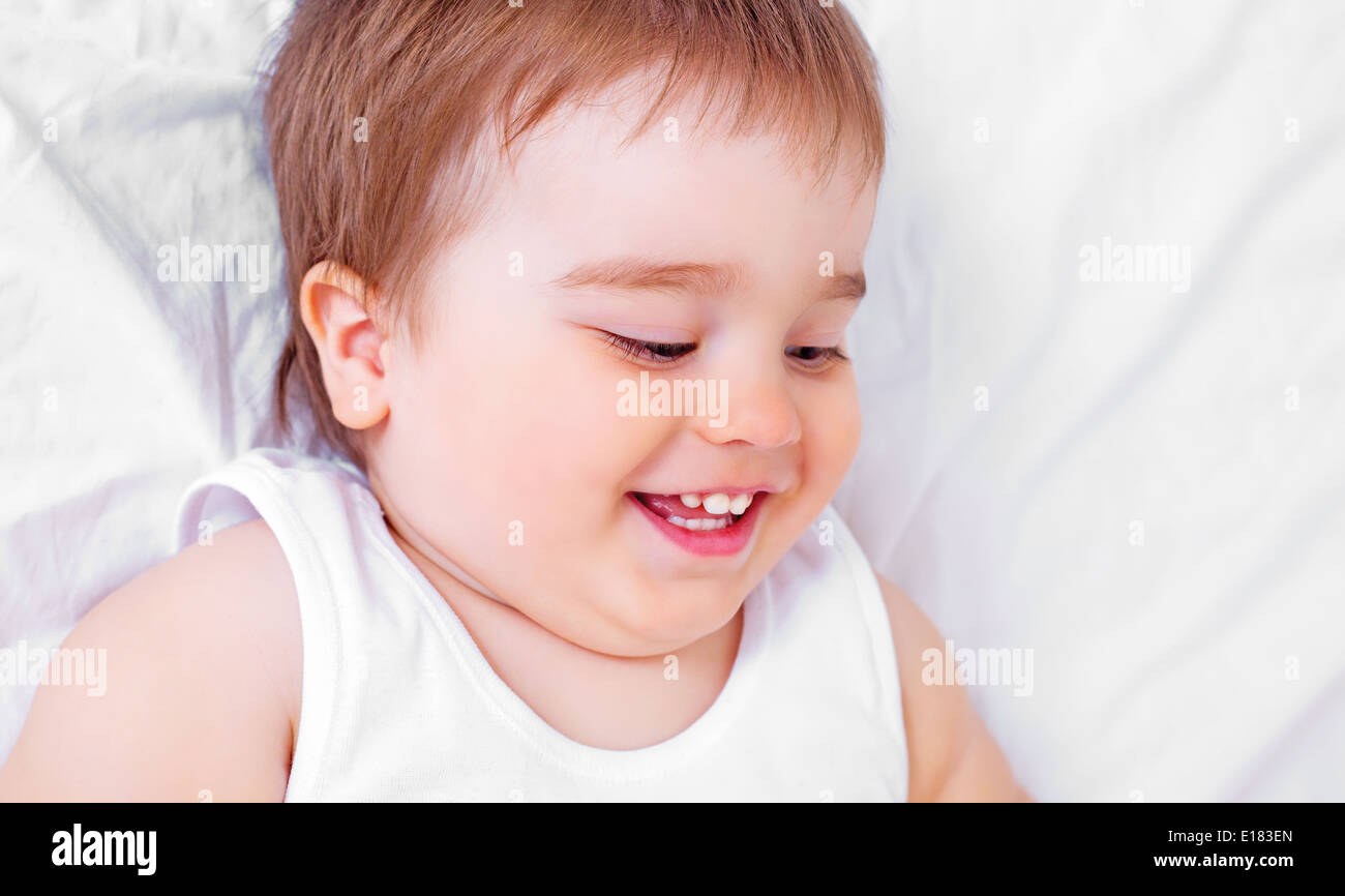 13245848b portrait of a happy laughing baby lying in bed at home