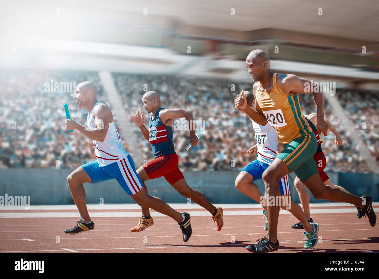 Relay runners racing on track Stock Photo