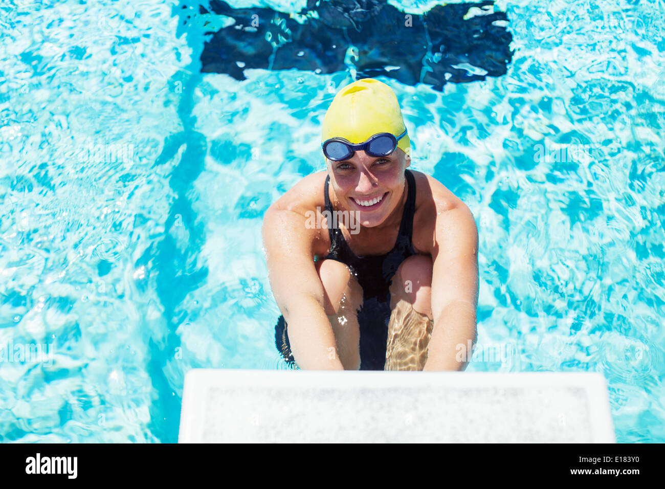 Portrait of smiling swimmer poised at starting block - Stock Image