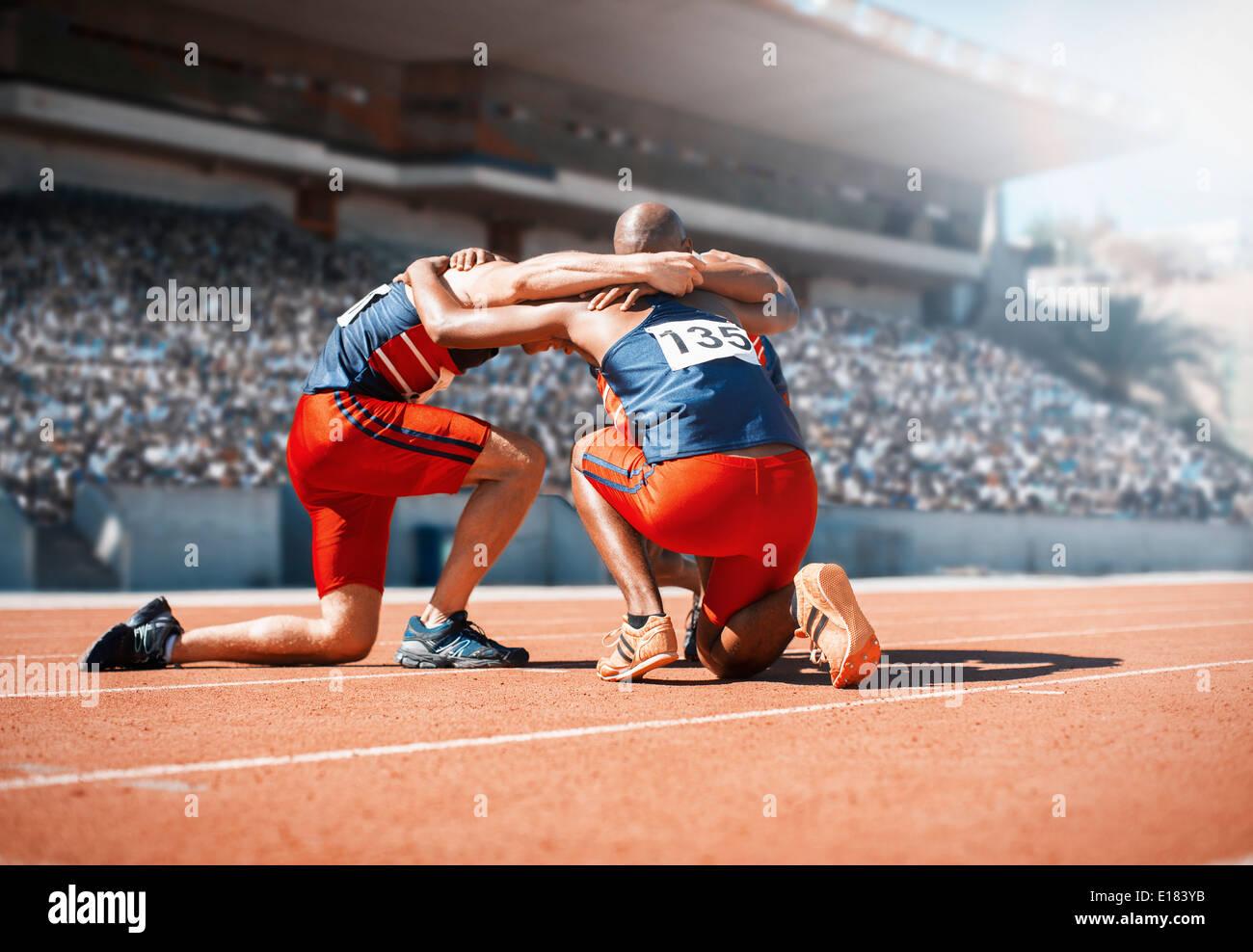 Runners huddled on track - Stock Image