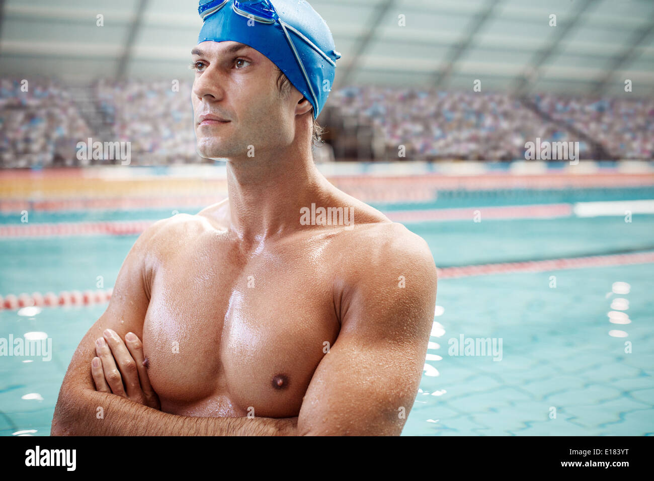 Serious swimmer standing poolside - Stock Image