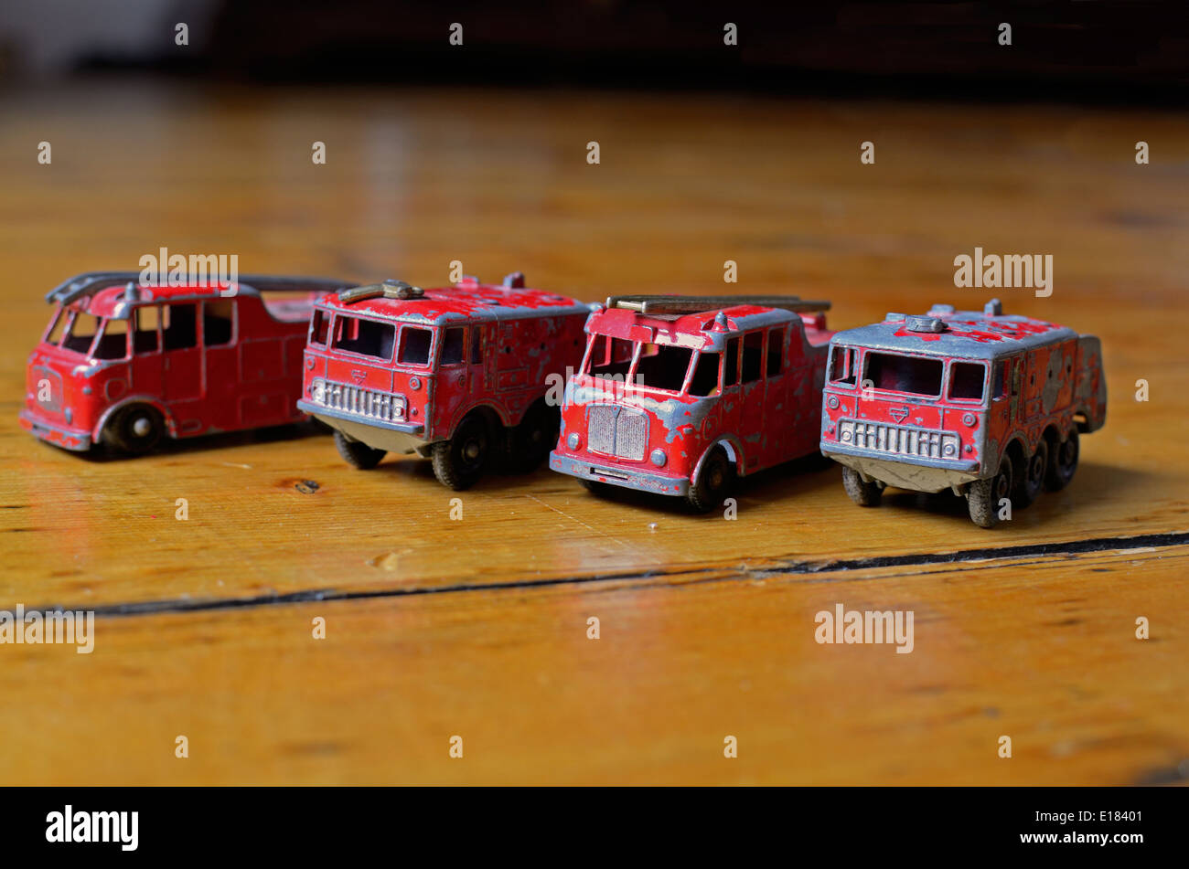 Four Matchbox toy fire engines lined up in a row on a wooden floor Stock Photo