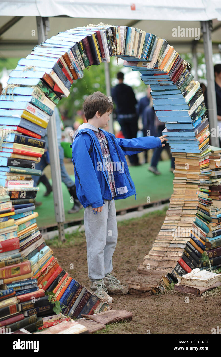 Hay on Wye, Wales UK, BANK HOLIDAY MONDAY 26 May 2014 A child boy looking at a sculpture made from old books and   enjoying the fifth  day of the 2014 Daily Telegraph Hay Literature Festival, Wales UK   photo ©keith morris - Stock Image
