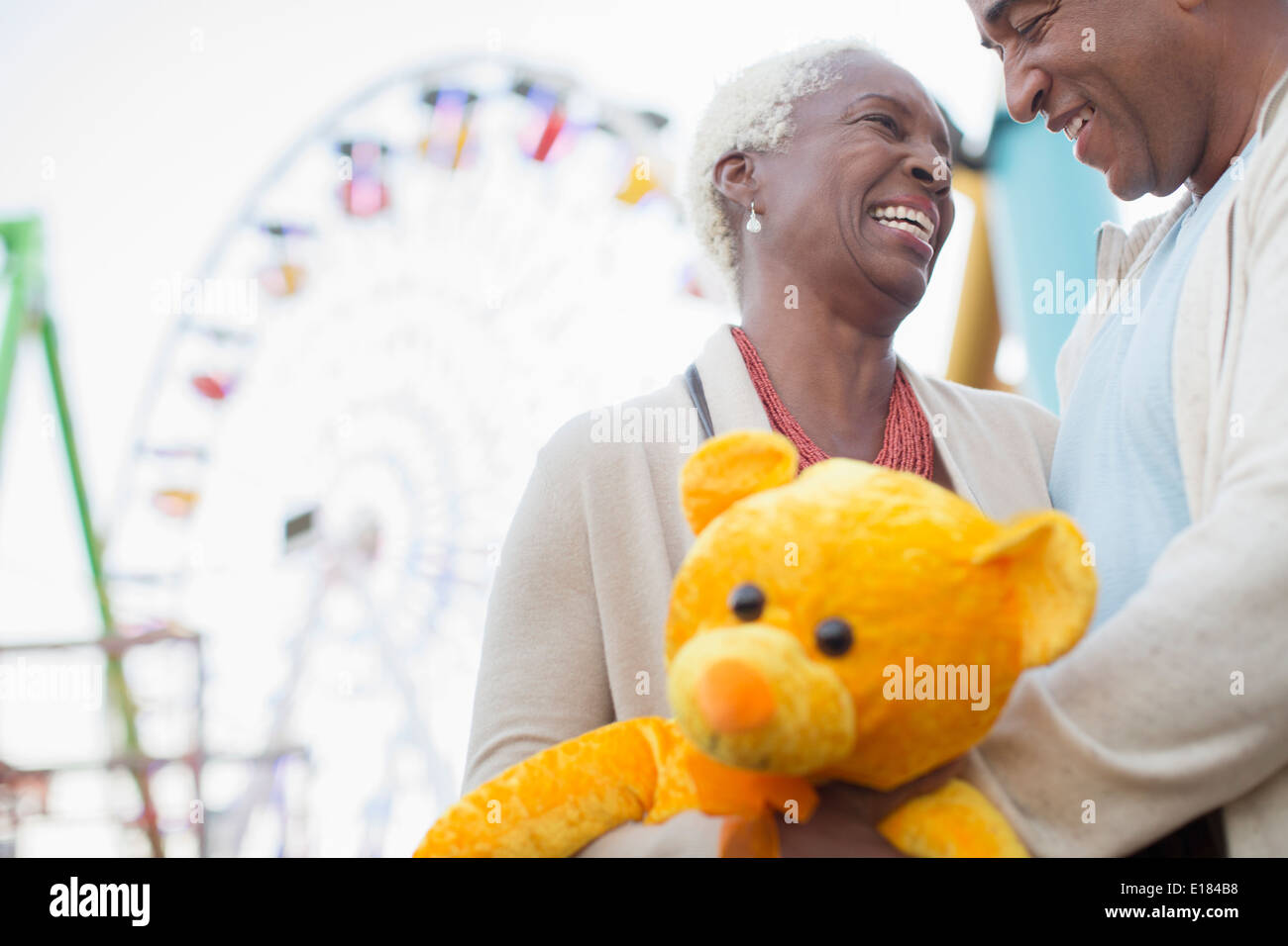 Senior couple with teddy bear hugging at amusement park - Stock Image