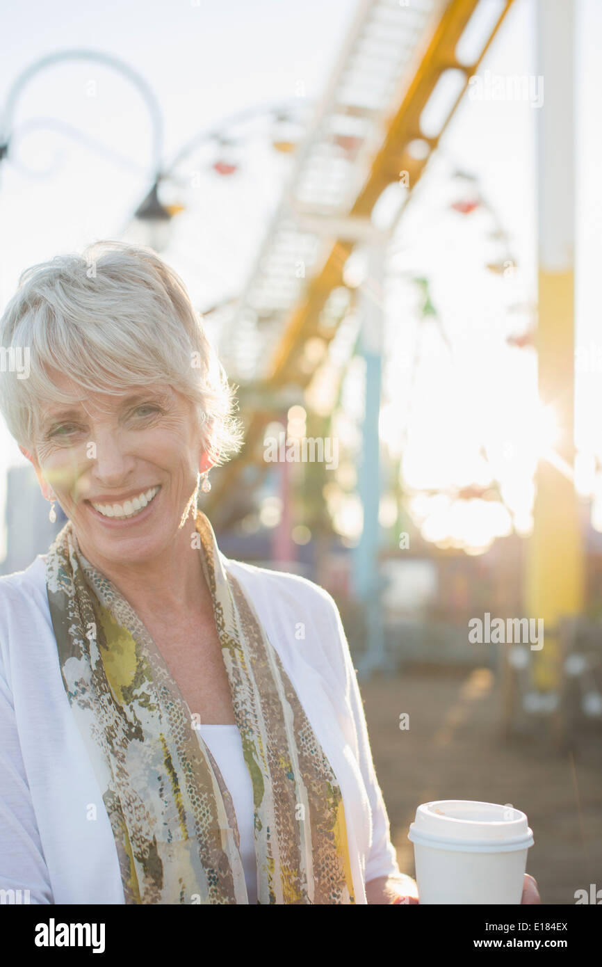 Portrait of smiling senior woman drinking coffee at amusement park - Stock Image