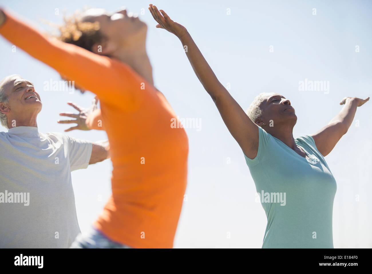 Seniors practicing yoga outdoors - Stock Image