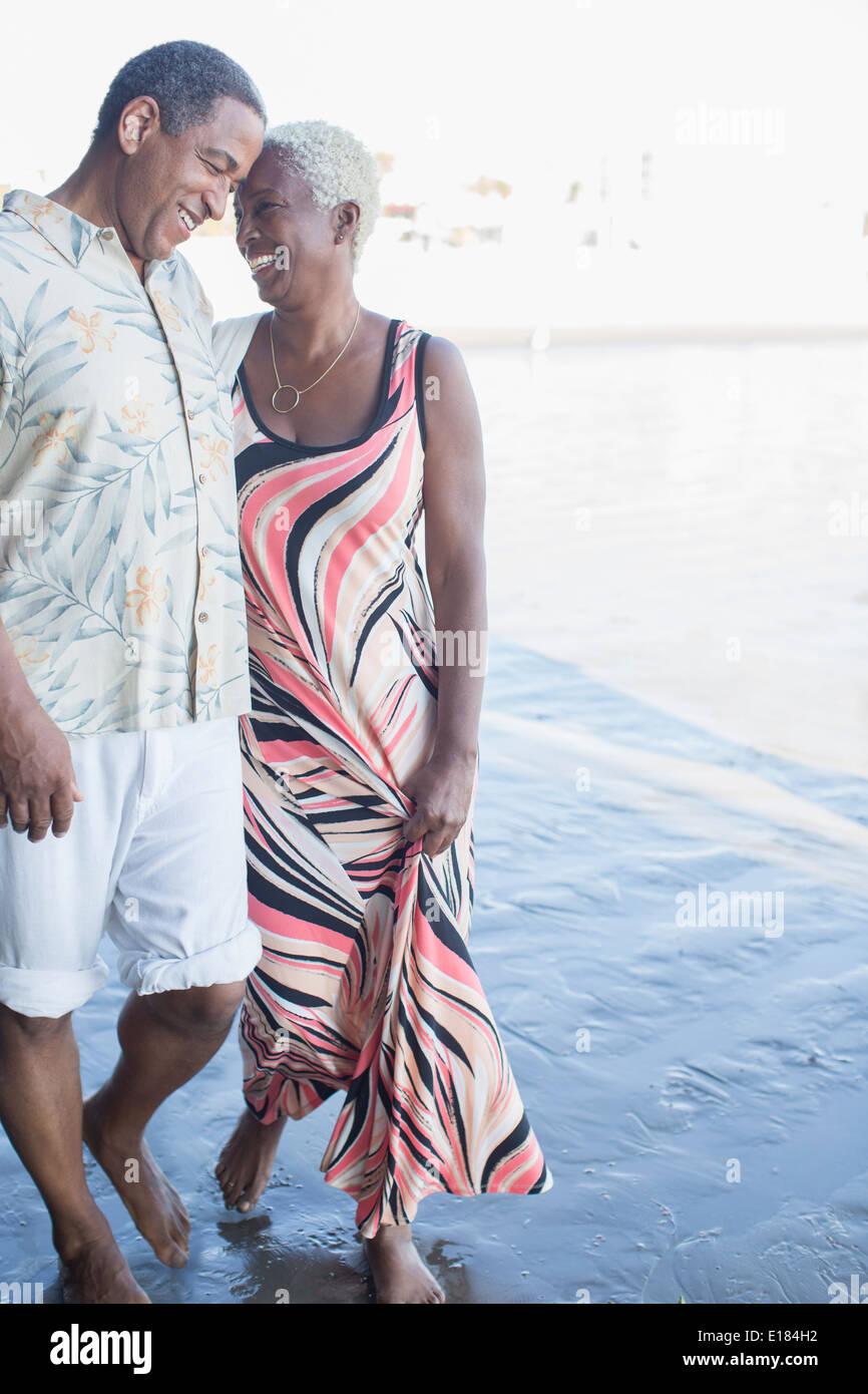 Senior couple walking barefoot on beach - Stock Image