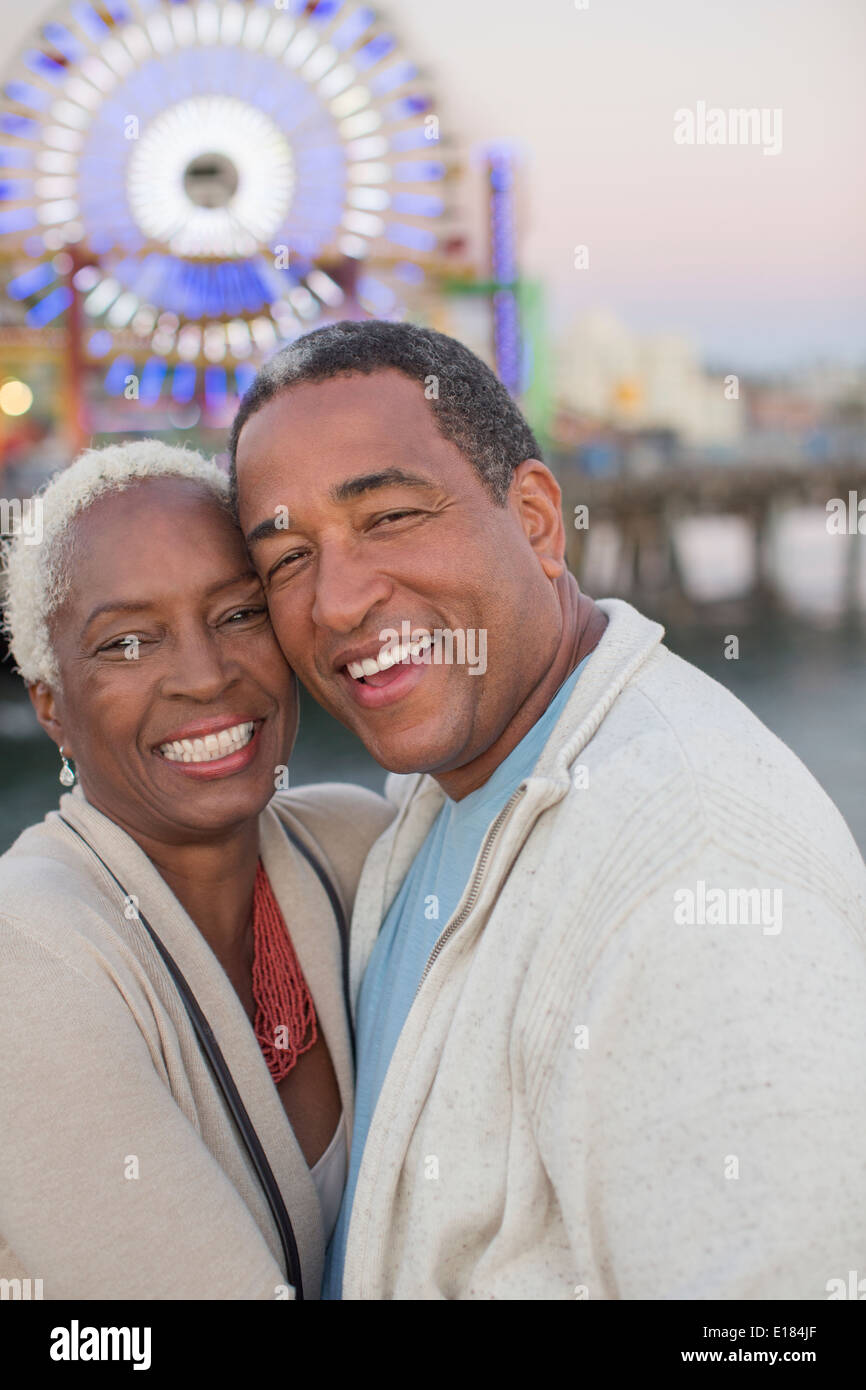 Portrait of happy senior couple at amusement park - Stock Image