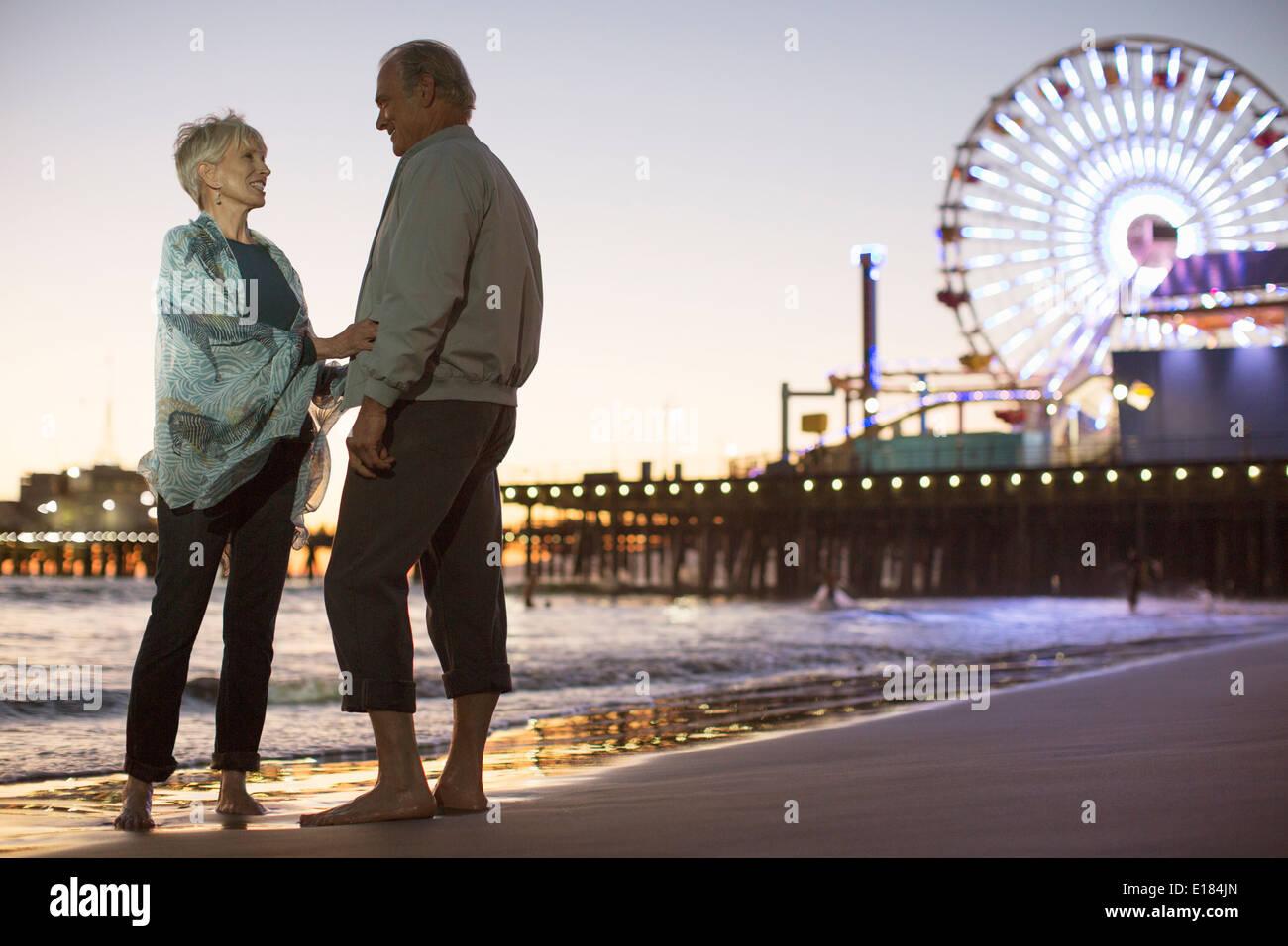Senior couple on beach at night - Stock Image