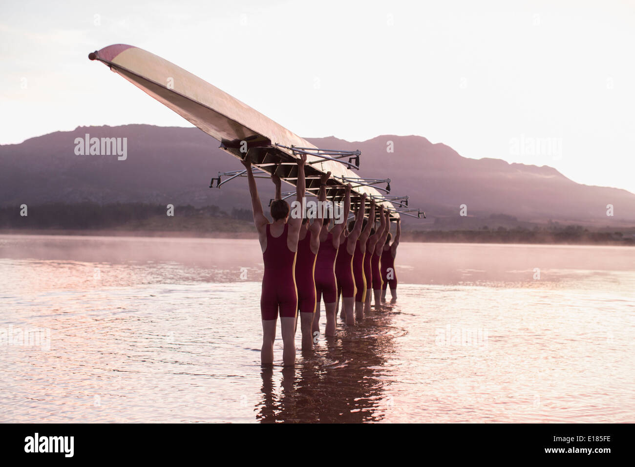 Rowing team carrying row boat overhead in still lake - Stock Image