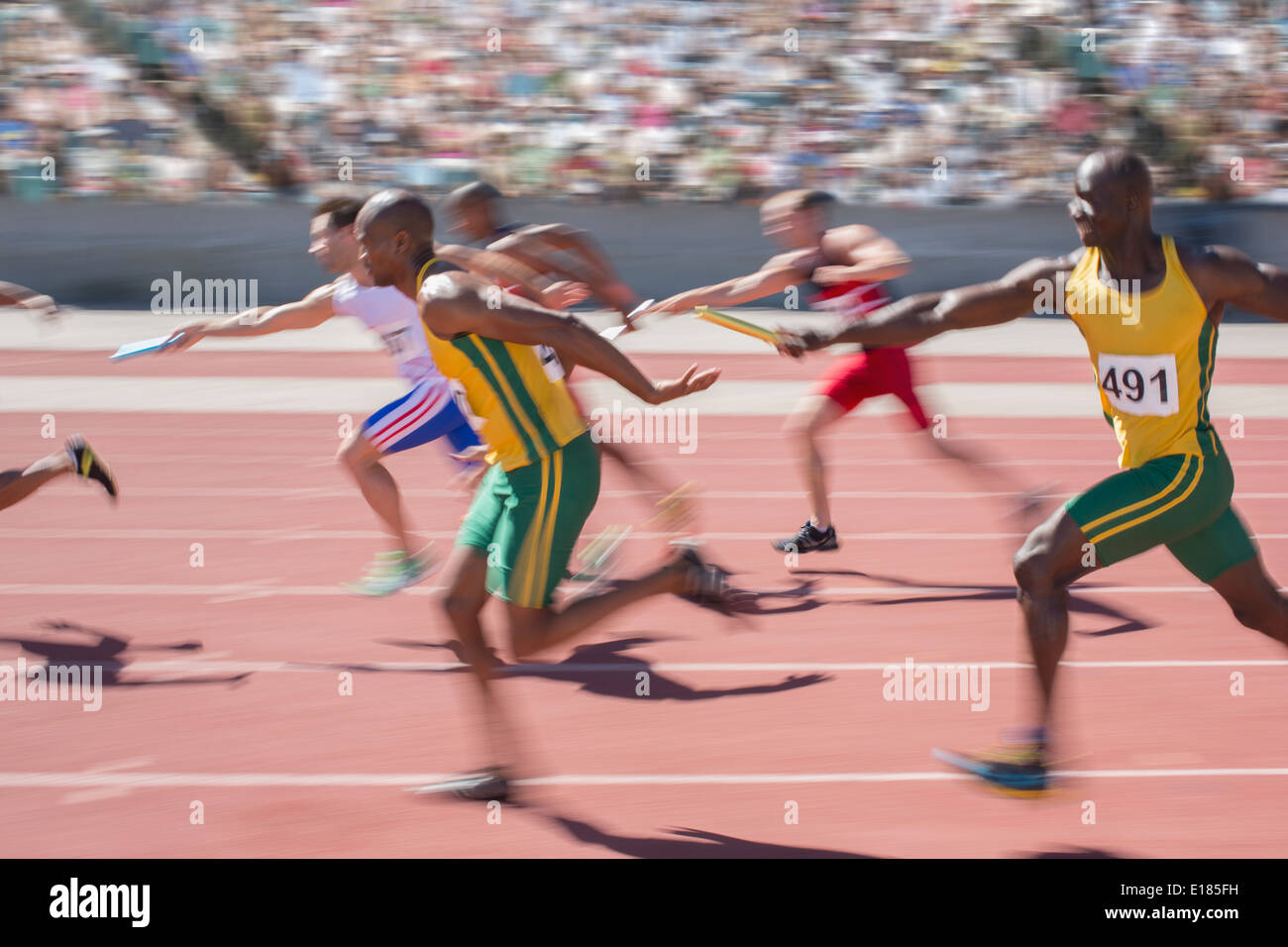 Blurred view of relay runners in race - Stock Image